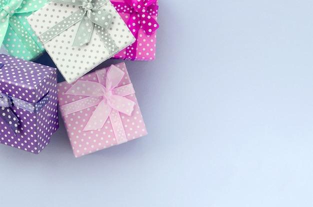 Pilha de um pequeno colorido caixas de presente com fitas encontra-se em uma violeta