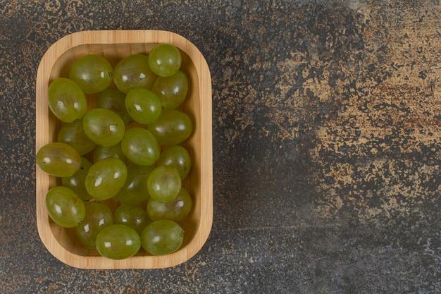 Pilha de uvas verdes na tigela de madeira.