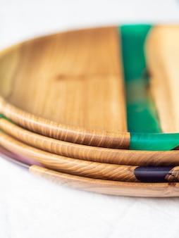 Pilha de várias bandejas redondas de madeira para artesanato com pastilhas de resina