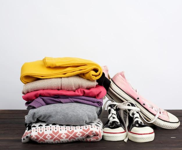 Pilha de várias roupas dobradas e cedwas têxteis usados em uma mesa de madeira
