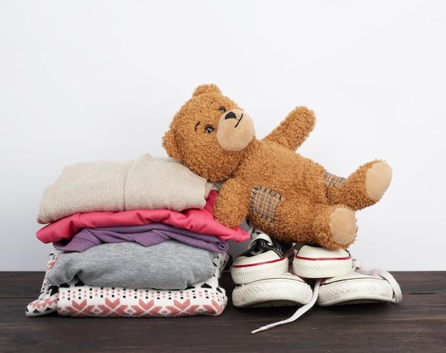 Pilha de várias roupas dobradas e tênis de têxteis usados em uma mesa de madeira