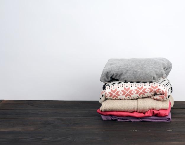 Pilha de várias roupas dobradas em uma mesa de madeira
