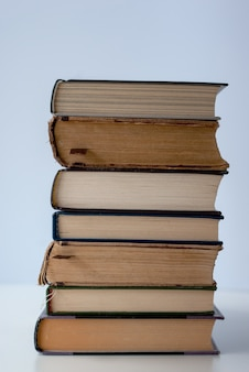 Pilha de vários livros antigos sobre fundo claro.