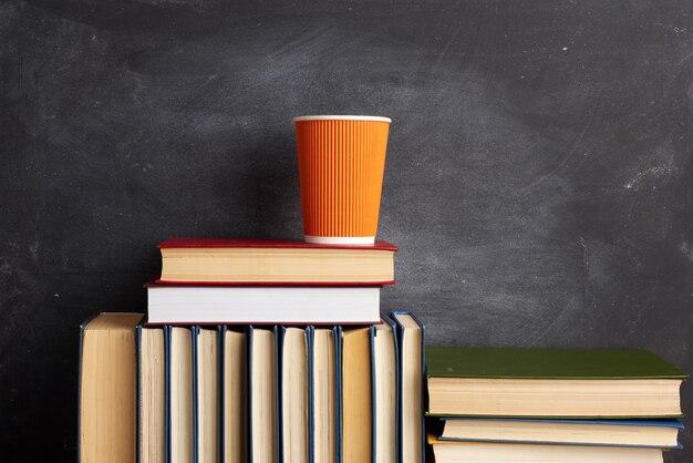 Pilha de vários livros e um copo descartável laranja com café em um quadro de giz preto