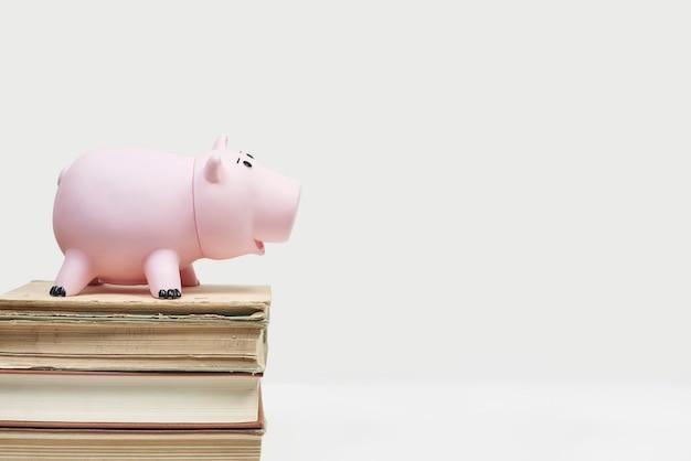 Pilha de velhos livros com mealheiro. custo da educação. economizando dinheiro para a faculdade. economize e pague pela educação infantil na faculdade