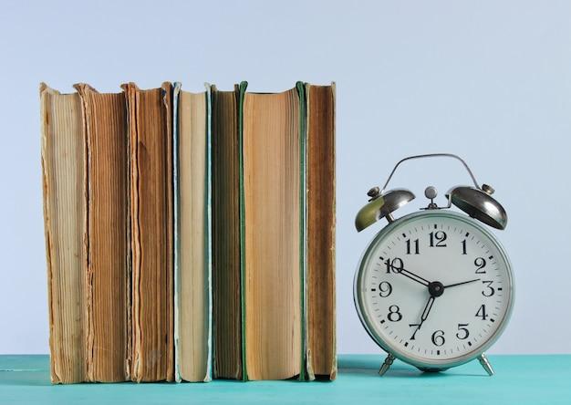 Pilha de velhos livros e despertador na prateleira de woden contra a parede branca