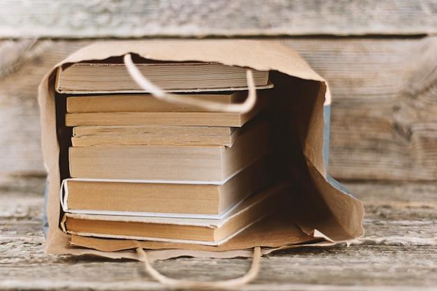 Pilha de velhos livros em saco de papel em fundo de madeira
