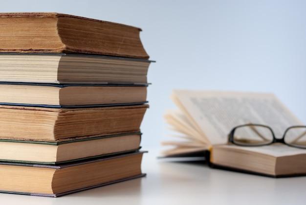 Pilha de velhos livros em uma mesa branca, um livro é aberto com óculos no topo.