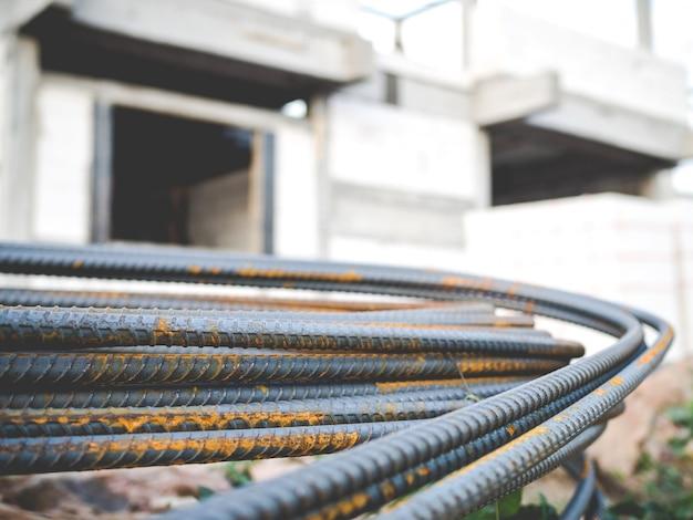 Pilha de vergalhões de aço para concreto de reforço com casa sob fundo de construção