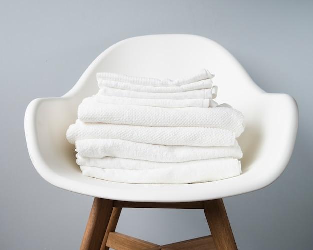 Pilha de vista frontal de toalhas em uma cadeira