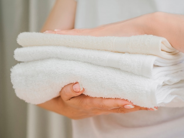 Pilha de vista lateral de toalhas entre as mãos