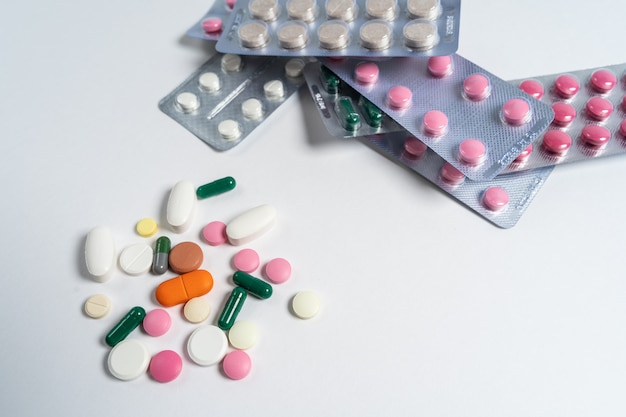 Pilha de vitaminas multicoloridas e comprimidos isolados em um fundo branco