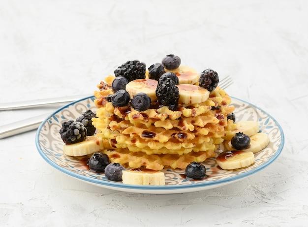 Pilha de waffles belgas assados em um prato redondo com frutas vermelhas em uma mesa branca, delicioso café da manhã, close-up