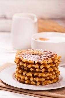 Pilha de waffles belgas grossos com pó do açúcar e copo do café do cappuccino.