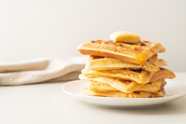 Pilha de waffles caseiros com manteiga e mel ou xarope de bordo