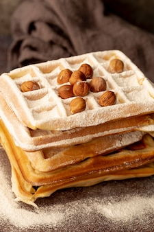 Pilha de waffles com açúcar em pó e avelãs