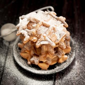 Pilha de waffles no prato com açúcar de confeiteiro