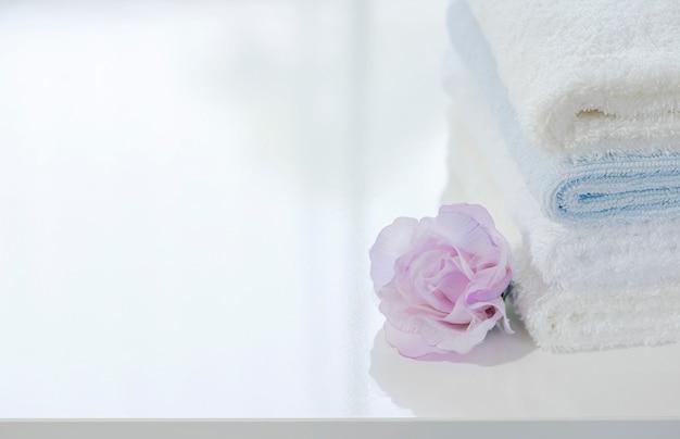 Pilha do close up das toalhas brancas e flor na tabela branca com espaço da cópia.