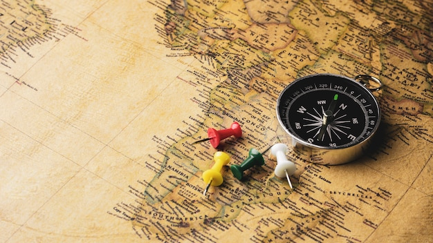 Pilha do compasso e do percevejo em um mapa antigo. - conceito de viagens e aventura.