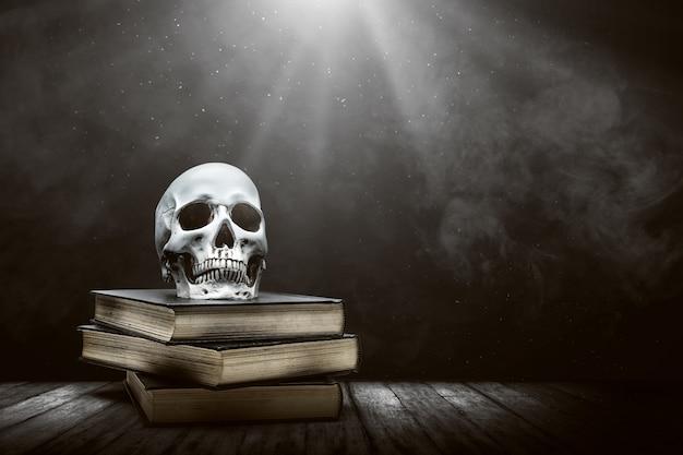 Pilha do livro com um crânio humano em uma mesa de madeira