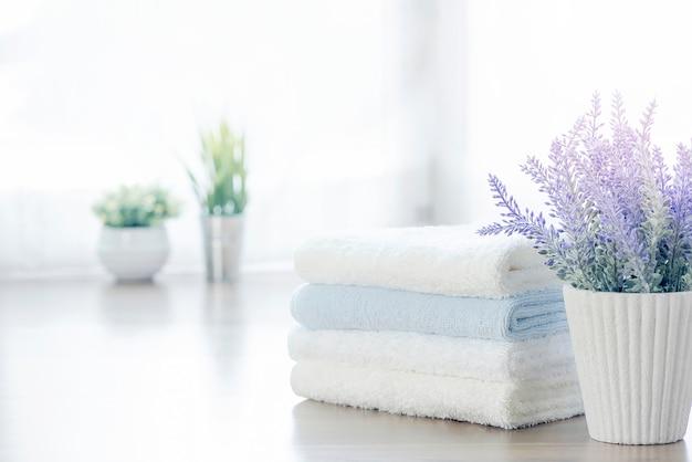Pilha do modelo das toalhas brancas e do houseplant na tabela branca com espaço da cópia.