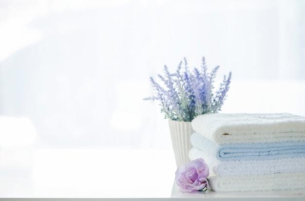 Pilha do modelo das toalhas e da flor brancas na tabela branca com espaço da cópia.