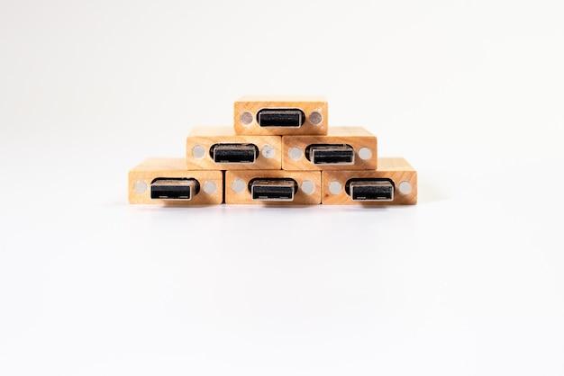 Pilha do usb pendrive de madeira da memória isolado no fundo branco.