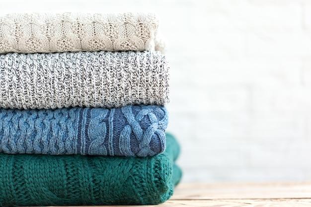 Pilha dobrada de camisolas de malha aconchegantes em fundo branco.