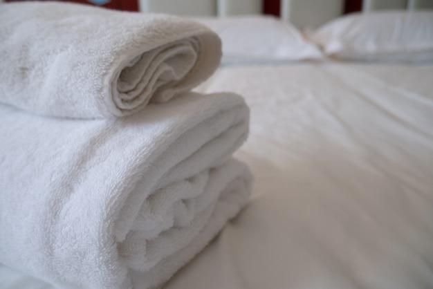 Pilha dobrada de toalhas brancas no quarto do hotel para o relaxamento acolhedor