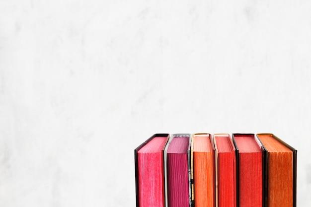 Pilha dos livros com a pilha da cor no fundo branco. espaço da cópia