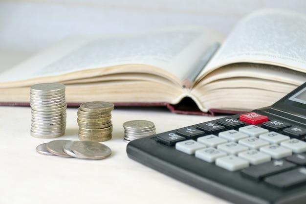 Pilha empilhada moedas, calculadora, livro aberto.