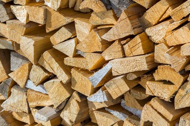 Pilha empilhada ordenadamente de madeira de troncos secos picados ao ar livre no inverno frio brilhante