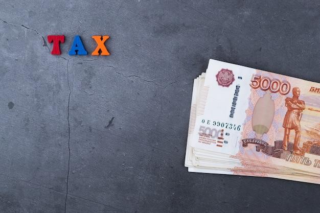 Pilha grande de cédulas do dinheiro do russo de cinco mil rublos que encontram-se em um cimento cinzento.
