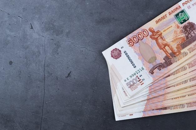 Pilha grande de cédulas do dinheiro do russo de cinco mil rublos que encontram-se no cimento cinzento.