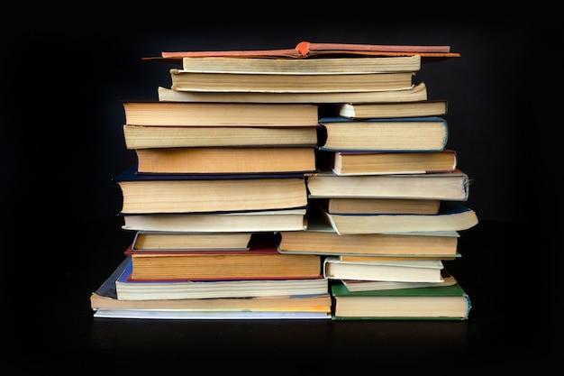 Pilha livros antigo fundo preto notebook biblioteca