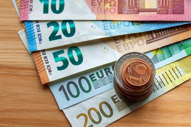 Pilha ordenada de notas de euro, notas de moeda no valor de dez, vinte, um e duzentos euros e diferentes moedas de metal. dinheiro, ocupação e finanças, conceito de investimento bem sucedido.