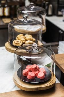 Pilha recentemente cozida de scones cor-de-rosa dentro da tampa da cúpula de vidro. coma com chá ou café. bons bolos.