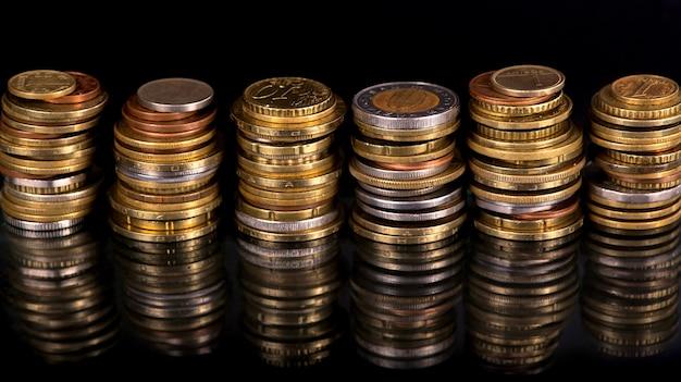 Pilhas cf moedas de países diferentes em fundo preto.