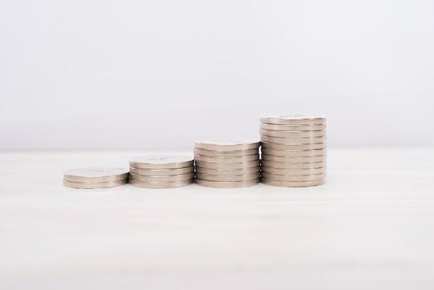 Pilhas crescentes de moedas em um fundo branco de madeira.