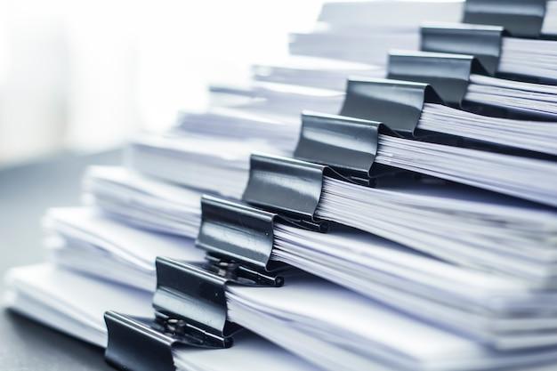 Pilhas de arquivos de documentos de papel de trabalho de escritório com clip preto.