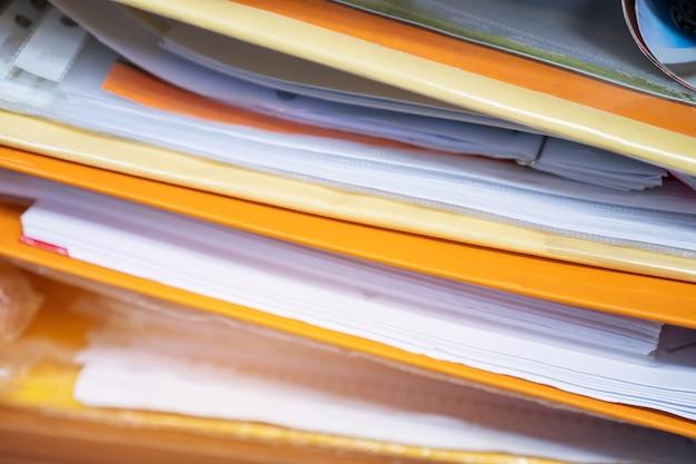Pilhas de arquivos de documentos, pastas de cor amarela para finanças no escritório.