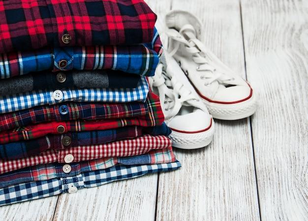 Pilhas de camisas quadriculadas e tênis