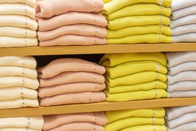 Pilhas de camisolas multicoloridas nas prateleiras na loja