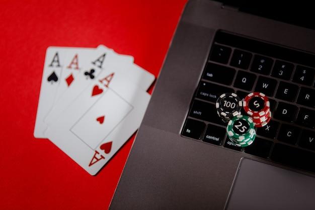 Pilhas de cartas de pôquer de fichas de pôquer e laptop em um conceito on-line de pôquer com fundo vermelho