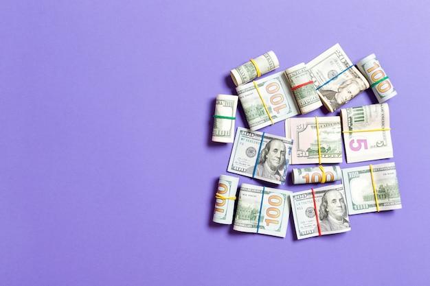 Pilhas de close de notas de cem dólares na vista superior roxa com espaço de cópia