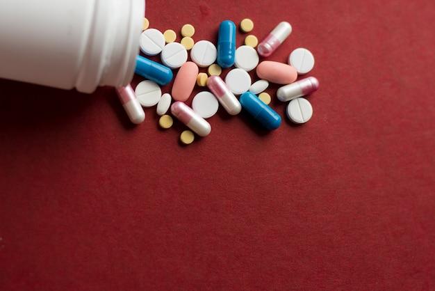 Pilhas de comprimidos e cápsulas em vermelho.