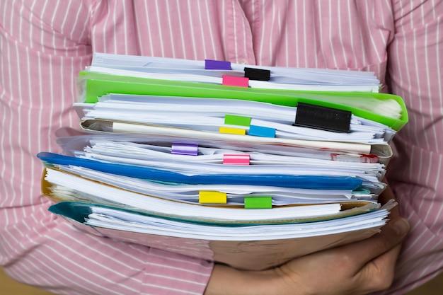 Pilhas de documentos em arquivos de papel nas mãos, documentos de relatório de negócios.