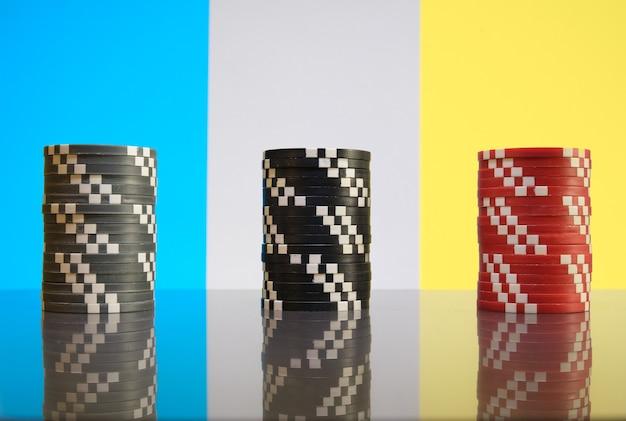 Pilhas de fichas de cassino vermelhas, pretas e cinza em close-up de fundo colorido.