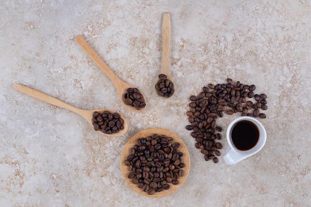 Pilhas de grãos de café e uma xícara de café