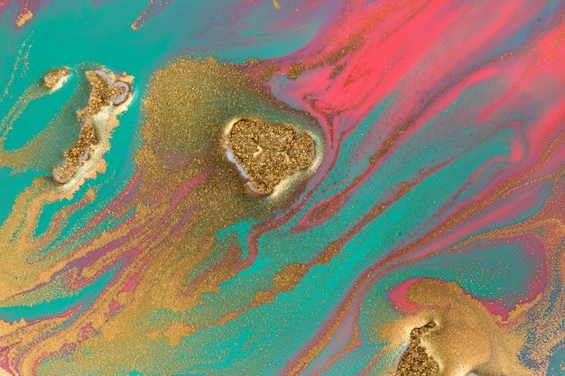 Pilhas de lantejoulas douradas em manchas de tinta rosa e azuis.